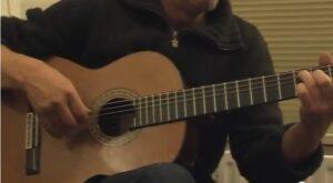 met gitaar op de bank